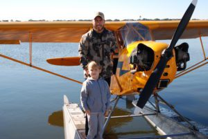 boy and flight instructor stand in front of Piper Cub on floats for seaplane lesson.